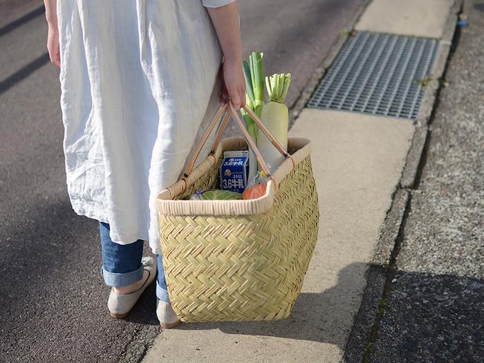 """こちらのかごも松野屋さんのもの。岩手県の山間部で採れる、丈夫でしなやかな篠竹を使い、熟練の職人がひとつずつ丁寧に編み上げた、元祖""""買い物バッグ""""といった感じの佇まいがたまりません。 東京の台所、築地市場などでは、この""""買い物バッグ""""を、プロの料理人が食材の仕入れに利用しているのを見かけることもあるんだとか…。 篠竹の表皮を剥き、節を取り、縦に四つに割ってから中の肉を取り除いて編んでいくかごは、あまり道具を使わず、指先のみできれいに仕上げられる、まさに職人の技から生まれる逸品です。"""