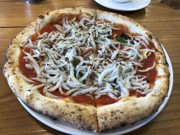大きなしらすがたっぷりの「しらすのマリナーラ」も人気です。石窯で焼くピザ生地は、もっちり感と香ばしさが絶妙。ニンニクの効いたトマトソースは、やみつきになるおいしさです。