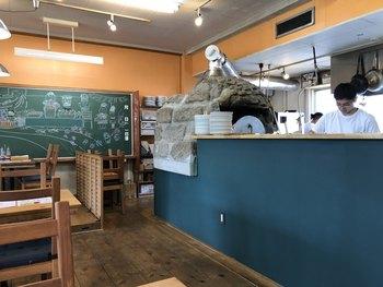 """校舎で本格的な薪窯ピッツァとイタリアンが楽しめるのが、「PizzeriaTrattoriaDaPeGONZO」です。カウンターの奥にある石窯は、地元・千葉の鋸山から切り出された""""房州石""""で作られているんですよ。"""