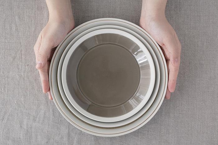 """こちらの器は、イイホシユミコさんと業務用のガラス製品を製造している""""木村硝子店""""のコラボレーション。 とことん丈夫で、使い勝手がよくて、用途が広い、業務用のいいところと、イイホシさんの世界感が表現された「dishes(ディシィーズ)」シリーズ。 プレートは全部で「180」「200」「220」「230」の4サイズ。サイズによってリムの立ち上がりの角度が異なり、盛り付けるお料理が映えるように設計されているそうです。どのタイプも縁にしっかりとした立ち上がりがあるので、汁気のあるものの盛り付けも安心です。"""