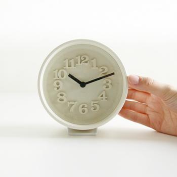 こちらの時計は、先程ご紹介したプロダクトデザイナー渡辺力さんが、1970年に発表した「小さい壁時計」の復刻モデル。  70年代、華やかな装飾の時計が数多くある中で、余計な装飾を省き、強い個性を表現したこの時計は、世界中の多くのデザイナーや建築家からも高く評価されていたそうです。  名前のとおり「小さな時計」は、直径約12cmとサイズも小ぶりで、レリーフ文字、針止めなど当時の雰囲気はそのままに、付属の専用スタンドを付ければ置時計としても使うことが出来ます。
