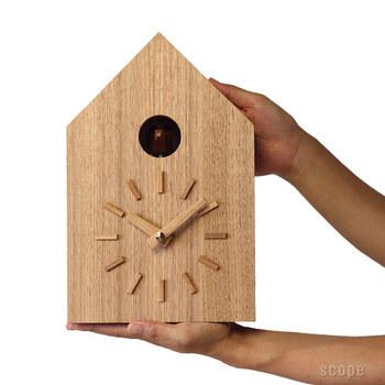 """こちらは人工林の保護を目的に活動する""""moreTrees""""の深澤直人さんデザインによる鳩時計。まるで森の中に佇む巣箱のような佇まいで、木目の入り方など、ひとつづつ異なる表情を見せてくれます。森林整備のため伐採されたモミ材とクルミ材で作られている鳩時計、時間を知らせる鳩の声は、笛を吹くように空気を押し出し音が鳴るふいご式。電子音とは違う、暖かい声が部屋中に響きわたります。 ディスプレイした時に見えるところは全て木製で、針や文字盤の装飾を省き、鳩の鳴き声を楽しむための時計のようです。 鳴き声をONにすると24時間、30分に1回、夜中でも関係なく、鳩が時間を知らせてくれます。"""