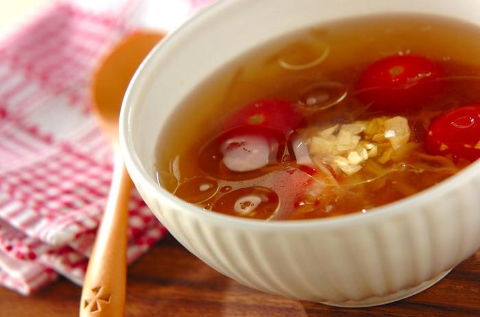 器に顆粒スープの素とプチトマト、コーン、市販の炒めた玉ねぎを入れてお湯を注いで作る、鍋を使わない簡単コンソメスープ。事前にニンニクをオリーブオイルに漬けた、ガーリックオイルを用意しておくだけで、ニンニクのアクセントがクセになる美味しいスープをあっという間に作れます。