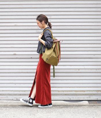 季節感のあるコーデュロイ素材のタイトスカートは、フロントに入った深めのスリットが特徴的な一枚。黒シャツと合わせたレディライクなコーディネートを、スニーカーとリュックで上手にカジュアルダウンしています。