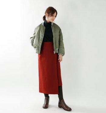 ラップ風デザインの巻きスカートに、黒のタートルネックトップスをタックインしたスタイリングです。カーキのライトアウターをプラスして、大人の最旬コーデが完成♪