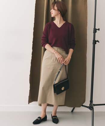 Vネックが女性らしい印象のボルドーニットに、ベージュのタイトスカートを合わせた着こなし。バッグやシューズの小物を黒でまとめることで、秋らしく大人っぽいコーディネートが完成します。