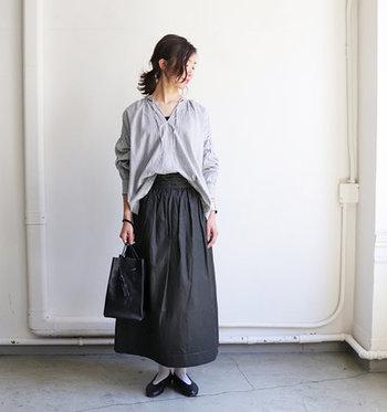 こちらのハリ感のあるコットン素材の黒スカートは、リボンの結び方でサイズ調整ができる巻きスカートタイプ。グレーのゆったりトップスを、フロントだけタックインするスタイリングで、シックとナチュラルの両立を叶えるコーディネートの完成です。