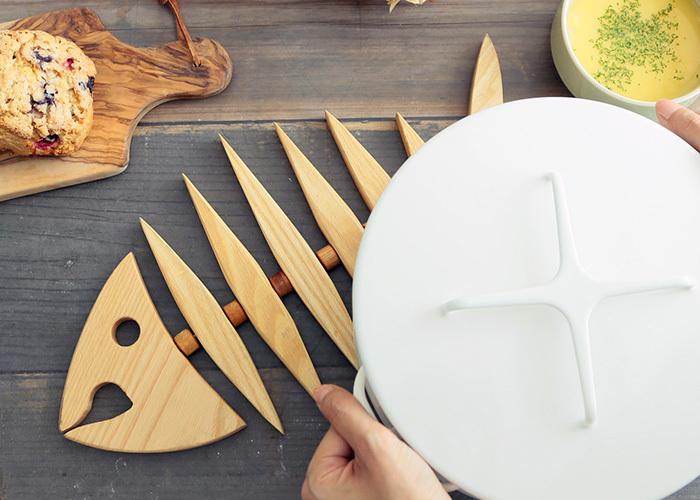 魚の骨をモチーフにしている鍋敷きは、木製で北欧テイスト漂うアイテム。収納時は壁に掛けると、骨の部分がカタカタと動き、遊び心のあるインテリアに早変わりします。