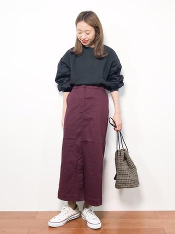 ワインカラーが印象的なタイトシルエットのスカートは、ストレッチ素材を使うことで動きやすさも抜群。黒トップスを合わせたダークトーンなコーディネートですが、白のスニーカーで明るさと、チェック柄のバッグで季節感をプラスしています。