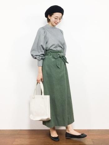 襟の幅が低めのハイネックは、すっきりとした印象に。オリーブ色のコーデュロイの巻きスカートにインして、着こなしにメリハリを。