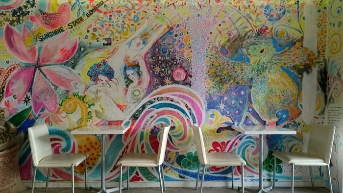 鮮やかなアートが描かれた壁が印象的。店内には18席、テラスに6席のイートインスペースがあります。