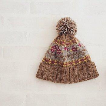 てっぺんのポンポンが可愛らしいニット帽。花柄ですが茶色ベースなので甘すぎず、お子様から大人まで幅広く対応できます。