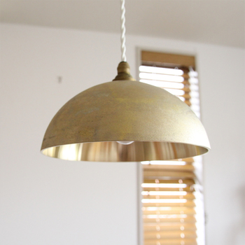 110年以上の歴史を持つ真鍮鋳物メーカー「二上」が立ち上げた生活用品ブランド「FUTAGAMI(フタガミ)」の鋳肌ペンダントランプは、丸みを帯びた半球型のシェードが特徴的。真鍮が放つ味わい深い輝きは、それだけで独特の存在感をがあります。 シェードの外側は、鋳造後の真鍮の表面をそのままに活かした鋳肌(いはだ)になっていて、ざらざらとした手触りです。内側は、ツルツルとした磨きがかかった削りだし仕様になっているので、外と内で真鍮の異なる質感と輝きを楽しむことが出来ます。真鍮の加工というのは、後から手直しがきかないそうなので、そこは、まさに熟練の職人の高い技術にかかっています。