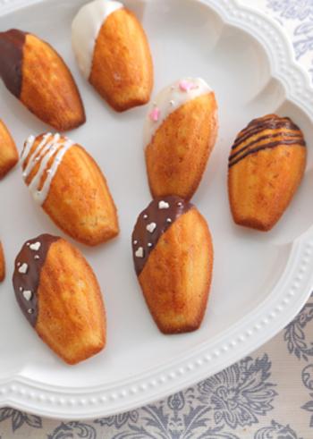 フランス発祥の焼き菓子、マドレーヌ。丸い形のものもありますが、やはり貝殻型がおなじみですね。プレーンなものを基本に、このレシピのようにオレンジピールを生地に加えたり、チョコレートをコーティングするなどアレンジ自在。デコレーションが可愛いですね。