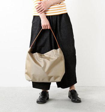 コンパクトなサイズ感に見えますが、大容量で荷物をたっぷり収納できるナイロン製のトートバッグです。一つ一つ丁寧に職人の手で作り上げられているので、暖かみを感じさせるデザインに仕上がっていますね。