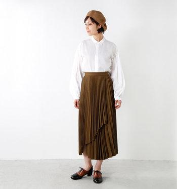 シンプルな白の長袖シャツは、ブラウンのアシンメトリーなプリーツスカートと合わせて。裾をたるませないタックインスタイルで、きちんと感をしっかり演出しています。