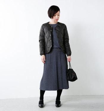 グレーのフェミニンなワントーンコーデにプラスしたいのがアクティブ要素を含んだ軽量の薄手ダウン。コートの下のインナーにもなります。スカート以外にデニムやチノパンとの相性も◎。ダイヤの形のキルティングとスナップボタンが可愛いですよね。スマートに着こなせる一着です。