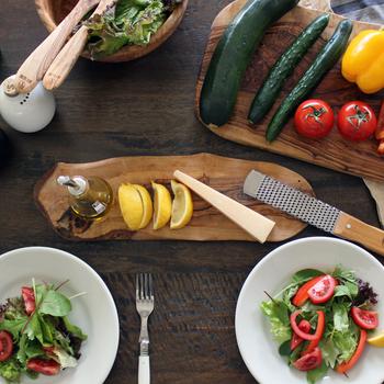 木製のカッティングボードも、テーブルで存在感を見せるアイテム。オリーブの木などは、表情豊かな木目や個性的な形など、どれひとつとして同じものがなく、料理をのせてテーブルの中央に据えるだけで視覚的なシンボルになります。