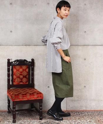 フロントの裾はラウンドデザインなのに、後ろ側はスクエアデザインになっている個性派シャツは、一枚で着るだけでおしゃれ顔が完成するアイテム。サイドには深めのスリットが入っているので、フロントだけのタックインも簡単に様になります。カーキのタイトスカートが、秋らしさをアップさせていますね。
