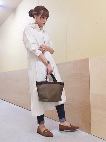 白のシャツワンピースに、デニムパンツとトートバッグを合わせたコーディネートです。シンプルナチュラルな着こなしに合わせて、バッグもシンプルなナイロントートをチョイス。シューズとバッグの色を合わせることで、着こなしに一体感を演出できます。