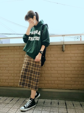 こちらもタータンチェックのスカートを合わせたコーデ。パーカーのダークグリーンも、秋らしくて素敵。休日の装いなら、このような遊び心を感じるロゴ入りパーカーをチョイスしてもいいですよね。