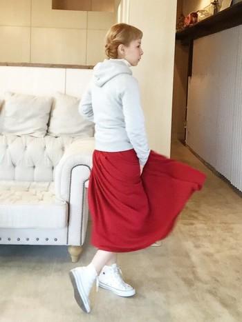 ぱっと目に入る赤いスカートがきれい*。薄いグレーのパーカーと、赤のロングスカートをあわせた、どこかフレンチカジュアルな色のコントラストを楽しめる着こなしです。足元のコンバースも、白に赤のラインが入っていて、全体の雰囲気をきれいにまとめていますね。