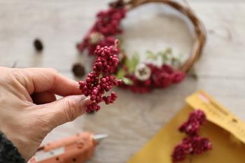 用意した花材をグルーガンで留め付けていきます。 全体のバランスを見て、大きな花材→小さな花材を取りつけていくのがおすすめです。 角度を変えて内側や外側にもバランスを見ながら配置しましょう。