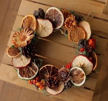 松ぼっくりとドライフルーツが印象的なリースは、リビングの主役になれそう♪ すき間に配置した小さな木の実が、平たいフルーツをより立体的に見せてくれます。