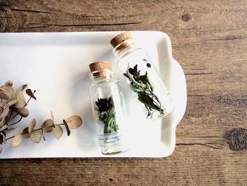 小さなビンにドライフラワーを閉じ込めたプチオブジェ。余った花材やカットした端材のアレンジにぴったりな方法です。グリーンや花を飾れない場所にも置くことができるのでおすすめの方法ですよ。