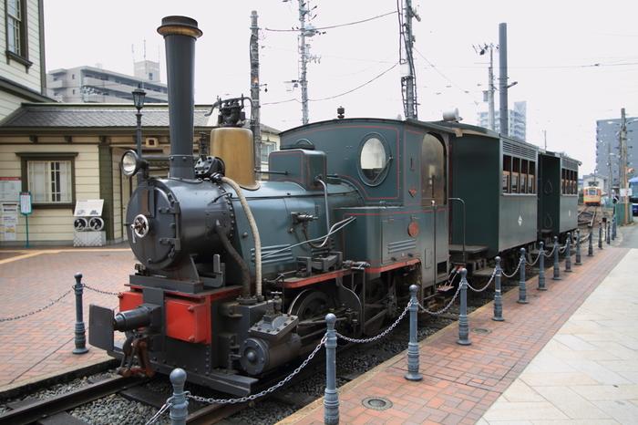 そばに停車中のレトロな列車。坊っちゃん曰く「マッチ箱の様な汽車」です。 明治21(1888)年から67年間にわたり活躍した蒸気機関車を平成13(2001)年に復元、『坊っちゃん』に登場したことにちなんで「坊っちゃん列車」と名付けられました。