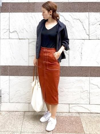 秋色タイトスカートに、白いプーマのスニーカーを合わせたコーデ。シンプルで大人っぽい装いを、より上品にかっこよく見せてくれるスニーカースタイルです。