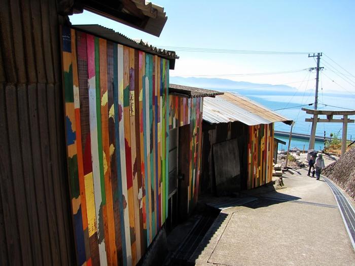 「男木島 路地壁面プロジェクト wallalley/眞壁陸二」。島で集めた廃材などに風景のシルエットをカラフルに描き、民家の外壁に設置された作品。島の路地のあちこちで見ることができますよ。散歩途中にこんな風景に出会えるなんて素敵ですよね。