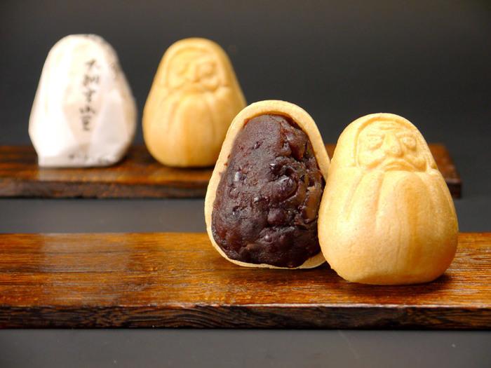 創業70年を超える真面目な和菓子屋「起き上がり本舗」が販売する「起き上がり最中」。ころんとした形が可愛らしいだるまの、シュールでシリアスな表情がユニーク。 北海道産の小豆を使用し、小豆そのものの甘みを楽しめる小倉あんと、静岡産の香り高い抹茶を使用した抹茶あん。とろりとした白あんの柔らかさを楽しむきんとん餡。お好みの味を選びたい。