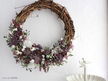 【日常になじむナチュラルな秋のリース】 紫のシックなミントフラワーや白のアンモビウムに、赤い野ばらの実を合わせた、秋らしい色合いのドライフラワーリース。土台の半分のみに花をあしらった落ち着いたデザインは、日常の暮らしにナチュラルになじみます。