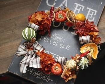 【ドライフルーツたっぷりの実りのリース】 木の実や、ライム・オレンジ・トウガラシ・かぼちゃなどのドライの実がたっぷりの秋のリース。シナモンなどもあしらって、温かなイメージに仕上がっています。