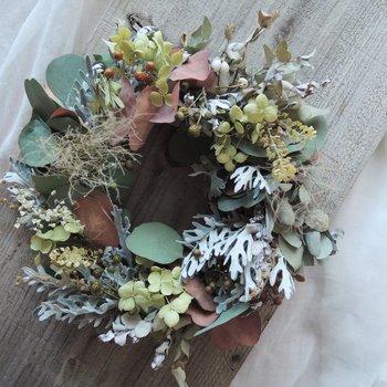 【ユーカリなどくすんだ秋色の植物を合わせて】 ベイクドカラー(焼いたようなくすんだ色)になったユーカリなど、秋の面持ちの植物をリースに。季節の訪れをリースで感じるのも素敵ですね。