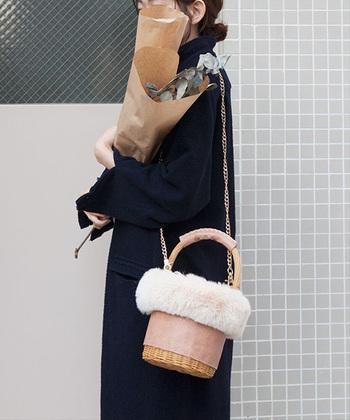 エコファーバッグで縁取られた、ショルダーにもなるかごバッグ。実はピンクの革部分はパイソン柄のフェイクレザーになっていて、甘くなりすぎない雰囲気がおしゃれです。