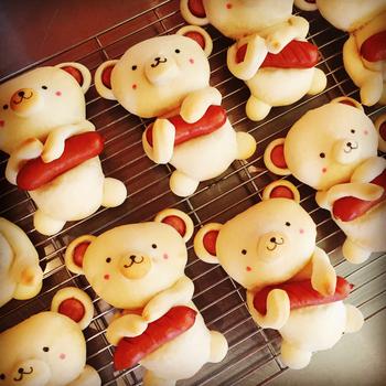 """まきパン(まきば)さんが作る""""くまさんのウィンナーパン""""は、食べてしまうのがもったいないくらいに可愛らしいちぎりパン。大好きなウインナーを大事そうに抱えたくまさんの姿が何とも愛らしく、ギフトとしても、お子さまのお誕生日などにもぴったり!ひとつひとつ微妙に異なる表情や、ウィンナーを持つ手も違い、まさに手作りならではの、ぬくもりが伝わって来る""""ほっこり""""心が和む一品です。"""