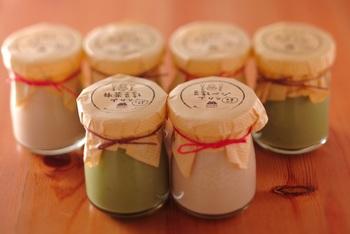 """京都・嵐山および、祇園鴨川でカフェを運営している「musubi-cafe」さんのこだわりの逸品""""有機豆乳プリン""""は、動物性食材不使用のベジプリンで、寒天を使用しているので繊維質もたっぷり!プリンといえば、卵や牛乳、クリームを使うものがほとんどですが、こちらのプリンは豆乳、てんさい糖といった植物性食材のみで作られているそうです。これなら、卵アレルギーの方も安心して食べることが出来ますね! 味は抹茶とプレーンの2種類。抹茶には、添付のきな粉をふりかけて、プレーンには黒糖蜜をとろ~りとかけてとろ~りプルプルを召し上がれ!"""