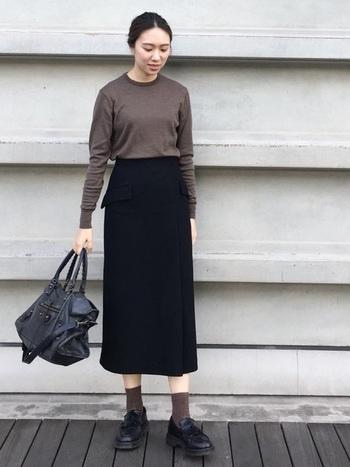 ブラウンがかったグレーのロングTシャツに黒のスカートを合わせたシンプルコーデ。上下タイトシルエットにまとめて縦長ラインを作ることで、大人っぽいイメージに。シックなカラーバランスが絶妙です。