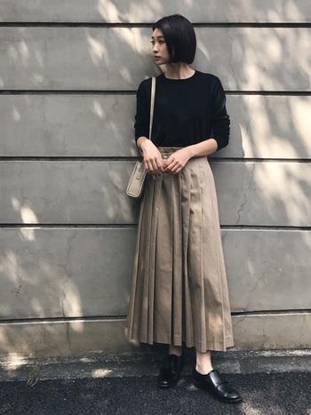 ベーシックな黒のロングTシャツは、チノプリーツスカートで程よいトレンド感をプラス。足元はトップスと同じ黒で引き締めて甘さを抑えたレディな着こなしに。