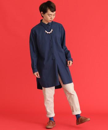 ちょっぴりオーバーサイズのチュニックシャツは、シンプルなシルエットだからこそ長めの丈でゆるっと着こなしたい一枚です。白のパンツと合わせた爽やかコーデに、ブルーのソックスをプラスしてまとまりのあるスタイリングに。