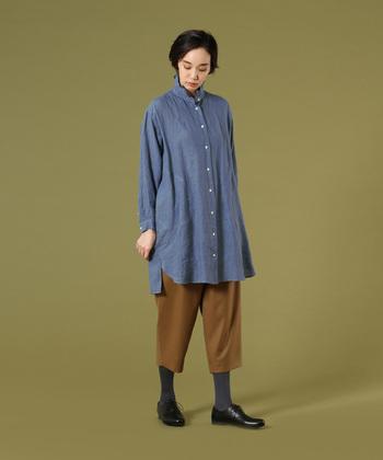 襟元にフリルをあしらったブルーのシャツチュニックは、カジュアルにもナチュラルにも着こなせる一枚。デニム風のトップスなので、どんなアイテムと合わせても好相性なのが嬉しいポイントですね。茶色のワイドパンツとグレーのタイツで、季節感のある着こなしの完成です。