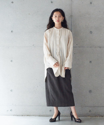 チュニック丈のシャツに、黒のタイトスカートを合わせたコーディネート。真っ白ではないキナリ色のトップス×黒ボトムスの組み合わせは、柔らかくナチュラルな印象を与えてくれます。黒のヒールパンプスを合わせて、レディライクな着こなしに。
