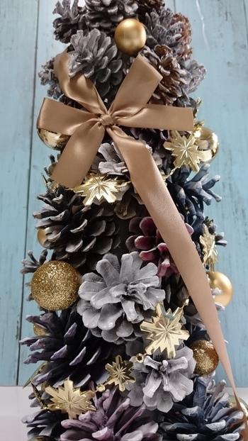 DIYでツリー作りを楽しむなら、小枝や松ぼっくりのような自然素材をふんだんに取り入れて。  松ぼっくりをいくつも重ねて存在感のあるツリーを作ってみましょう。 大きなリボンやゴールド系のパーツで飾り付ければ、今年らしいツリーになります。