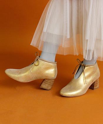 脚をキレイに見せたいけど、ヒールは歩きにくいと感じる女性にぴったりなチャンキーヒールのブーツ。キラリと輝くゴールドのブーツは、シックなコーデやナチュラルコーデに合わせてワンポイントにしても◎
