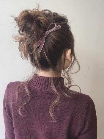 後れ毛たっぷりのお団子ヘアに、ベロア調のリボンで大人レトロな雰囲気をプラス。 リボンをお団子の根本にくるっと巻き付けて、斜め後ろの位置で結ぶことで上品で控えめな印象に。