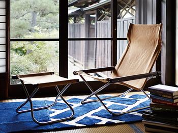 アウトドアでも活用する折りたたみチェアーを、窓辺で寛ぐ安楽椅子として、読書や昼寝を楽しもう。