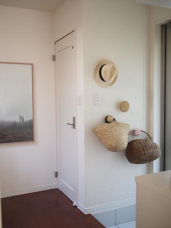 玄関横の壁にフックを取り付けるアイデア。まあるい木製のフックなら、使っていない間でも玄関をナチュラルでおしゃれな空間に見せてくれます。