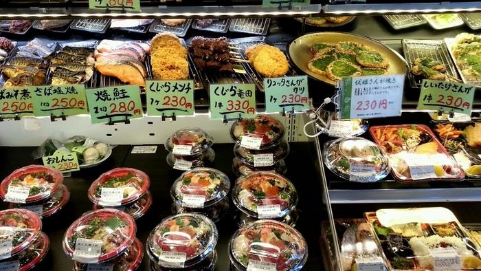 建物2階の惣菜店も「富楽里とみやま」で賑わうスポット。 弁当や惣菜が所狭しと並ぶ「青倉」と、喫茶軽食の「菜の花」は、房総ならではの郷土の味を手軽に味わえるお店です。 【画像は「青倉」のショーケース。この店の名物は、上段右側の『さんが焼き』。】